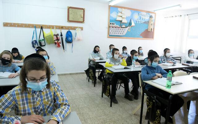 Des enfants Haredim de l'école ultra-orthodoxe Bnei Moshe Kretchnif portent des masques dans leur école de la ville de Rehovot, le 24 mai 2020. (Yossi Zeliger/Flash90)