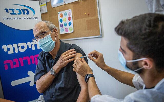 Un Israélien se fait administrer une piqûre de rappel dans un centre de vaccination de la caisse Maccabi, le 1er août 2021. (Crédit : Yonatan Sindel/Flash90)