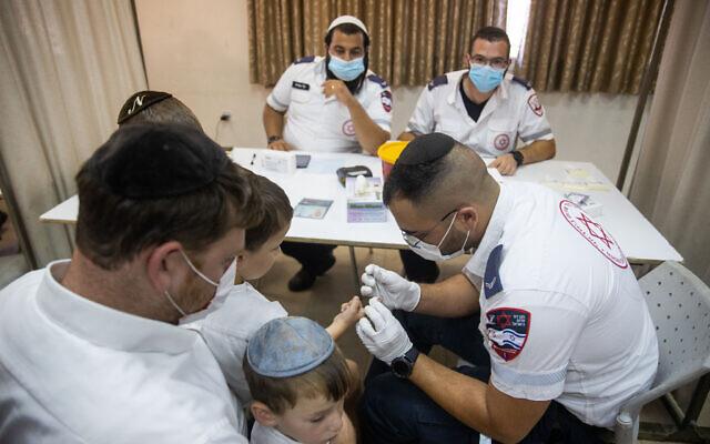 Un employé du Magen David Adom prélève le sang d'un enfant pour effectuer un test sérologique dans la ville ultra-orthodoxe de  Kiryat Yearim, aux abords de Jérusalem, le 9 août 2021. (Crédit :  Yonatan Sindel/Flash90)