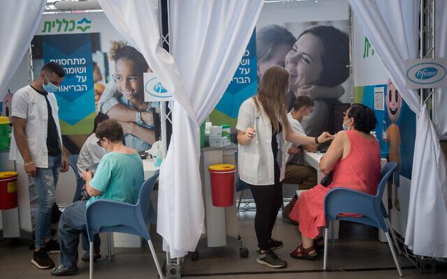 Des Israéliens de plus de 60 ans reçoivent leur injection de rappel contre la COVID-19 dans un centre temporaire de vaccination de la Clalit à Tel Aviv, le 10 août 2021. (Crédit : Miriam Alster/Flash90)