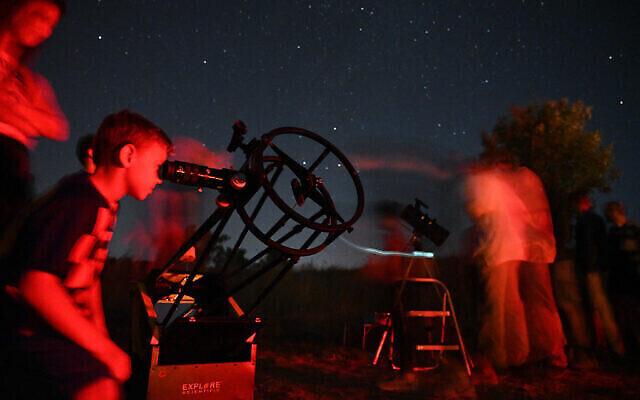 Des Israéliens regardent les étoiles pendant une pluie de météorites au-dessus du plateau du Golan, le 13 août 2021. (Crédit : Michael Giladi/Flash90)