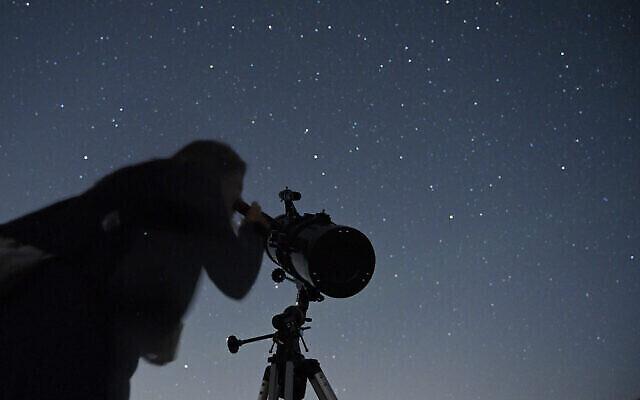 Un Israélien regarde les étoiles pendant une pluie de météorites au-dessus du plateau du Golan, le 13 août 2021. (Crédit : Michael Giladi/Flash90)
