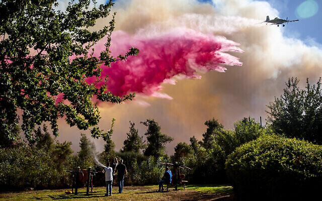 Des avions bombardiers d'eau tentent d'éteindre les flammes qui dévorent une forêt à proximité de Beit Meir, le 15 août 2021. (Crédit : Yonatan Sindel/Flash90)