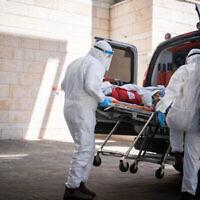 Des employés du Magen David Adom évacuent un patient soupçonné d'être atteint par la  Covid-19 à l'hôpital Hadassah Ein Karem de Jérusalem, le 15 août 2021. (Crédit :  Yonatan Sindel/Flash9)