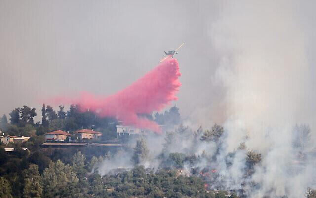 Un avion bombardier d'eau tente d'éteindre un incendie à Givaat Yearim, aux abords de Jérusalem, le 16 août 2021. (Crédit :  Yonatan Sindel/Flash90)