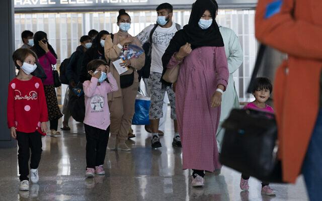 Des familles évacuées de Kaboul, en Afghanistan, traversent le terminal avant de monter dans un bus après leur arrivée à l'aéroport international de Washington Dulles, à Chantilly, en Virginie, le mercredi 25 août 2021. (Crédit : AP Photo/Jose Luis Magana)