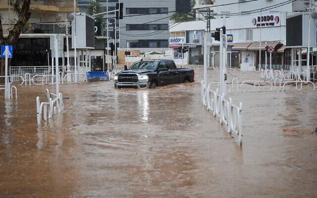 Une voiture roule sur une route inondée dans la ville de Nahariya, au nord d'Israël, le 8 janvier 2020, après qu'une rivière soit sortie de son lit. Environ 40 %, soit 250 millimètres (9,8 pouces), des précipitations annuelles moyennes de la ville sont tombées du 3 au 9 janvier de cetteannée-là. (Crédit : Meir Vaknin/Flash90)