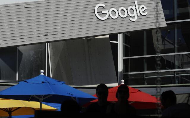 Sur cette photo d'archive du 24 septembre 2019, des personnes passent devant un panneau Google sur le campus de Mountain View, en Californie (Crédits : AP Photo/Jeff Chiu, File).