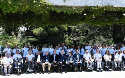 La délégation paralympique israélienne à Tokyo pose pour une photo avec Reuven Rivlin, alors président d'Israël, le 23 juin 2021 à Jérusalem. (Crédit : Amos Ben Gershom / GPO)