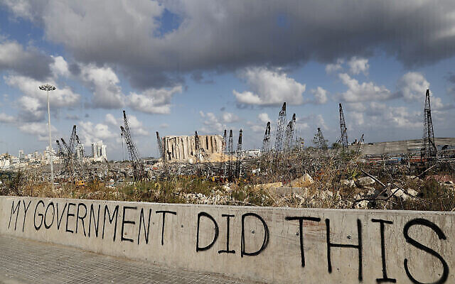Des graffitis politiques sont visibles devant le lieu de l'explosion du 4 août qui a touché le port maritime de Beyrouth, au Liban, le 9 août 2020.(Crédit : AP/Hussein Malla)