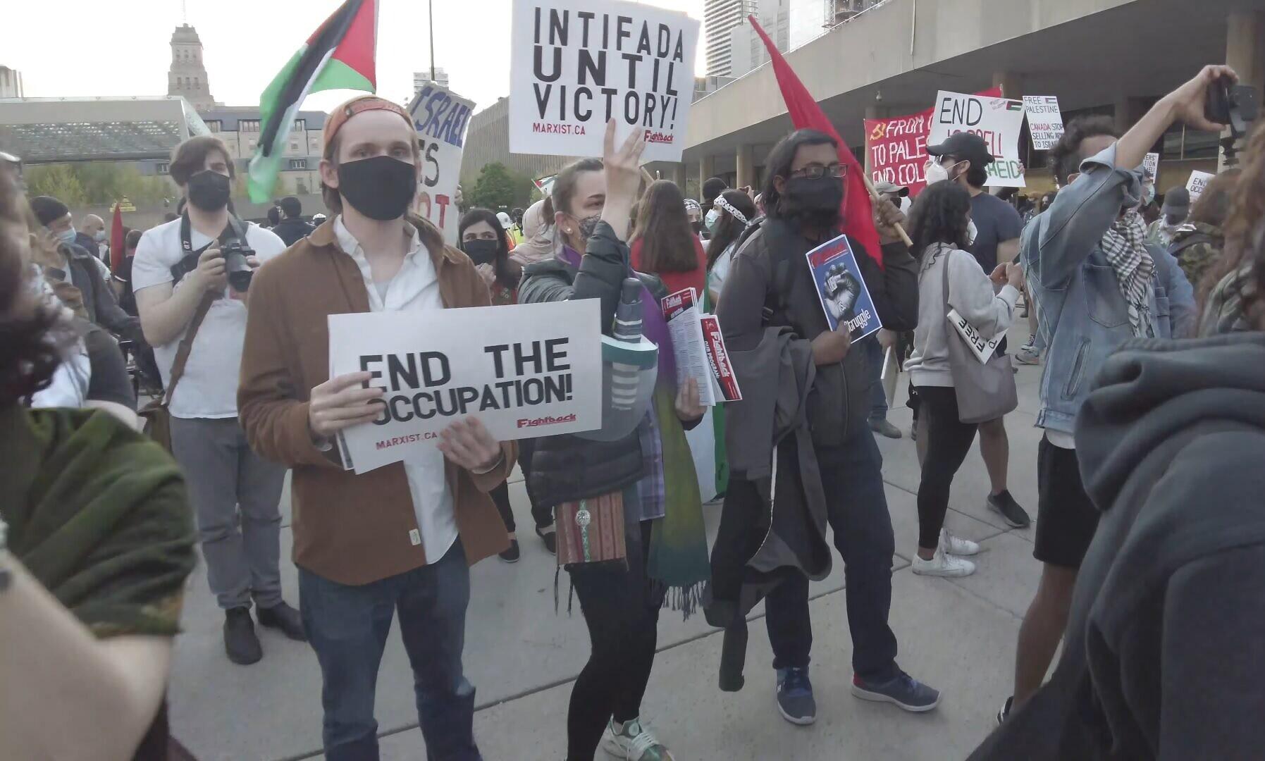 """Une femme tient une pancarte sur laquelle on peut lire """"Intifada jusqu'à la victoire"""" lors d'un rassemblement pro-palestinien organisé pendant l'opération israélienne """"Gardiens des murs"""", au square Nathan Phillips, dans le centre-ville de Toronto, le 15 mai 2021. (Crédit : capture d'écran YouTube)"""