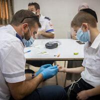 Un employé du Magen David Adom a effectué un test sérologique pour le COVID-19 dans la ville ultra-orthodoxe de Kiryat Ye'arim, le 9 août 2021 (Crédit : Yonatan Sindel/Flash90)