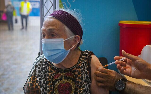 Une femme israélienne de plus de 60 ans reçoit une troisième injection de vaccin contre le coronavirus dans une clinique de santé Clalit à Jérusalem, le 8 août 2021. (Crédit : Olivier Fitoussi/Flash90)