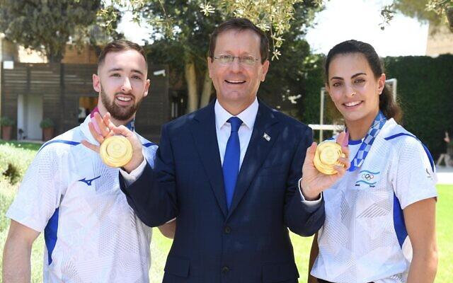 Artem Dolgopyat (G), le président Isaac Herzog (C) et Linoy Ashram (D) avec leurs médailles d'or olympiques à la résidence du président à Jérusalem, le 16 août 2021 (Crédit : Itay Beit-On/GPO).