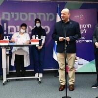 Le Premier ministre Naftali Bennett s'exprime à l'hôpital Sheba de Tel Hashomer lors du lancement de la campagne de rappel du vaccin contre le coronavirus. A sa droite, le président Isaac Herzog. (Crédit : Haim Zach / GPO)