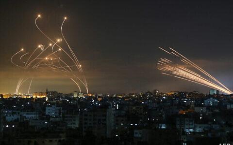 On aperçoit dans le ciel nocturne des roquettes provenant de Gaza, à droite, tirées en direction d'Israël depuis Beit Lahia, dans le nord de la bande de Gaza, le 14 mai 2021, tandis que des missiles d'interception Dome de Fer, à gauche, se dressent à leur rencontre. (Crédit : Anas Baba/AFP)