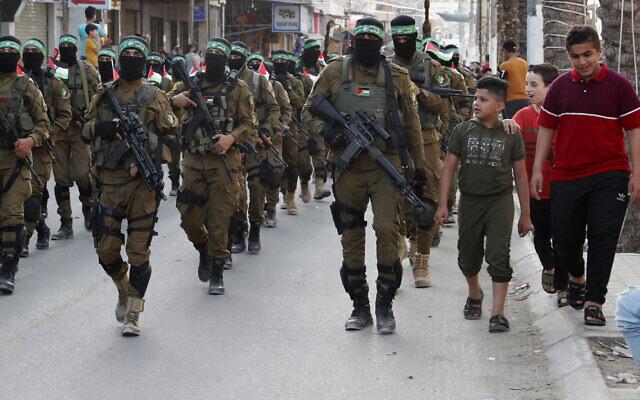 Des enfants discutent avec des membres masqués de l'aile militaire du Hamas, lors d'une marche dans les rues du camp de réfugiés de Nusseirat, dans le centre de la bande de Gaza, le 28 mai 2021. (Crédit : AP Photo/Adel Hana)