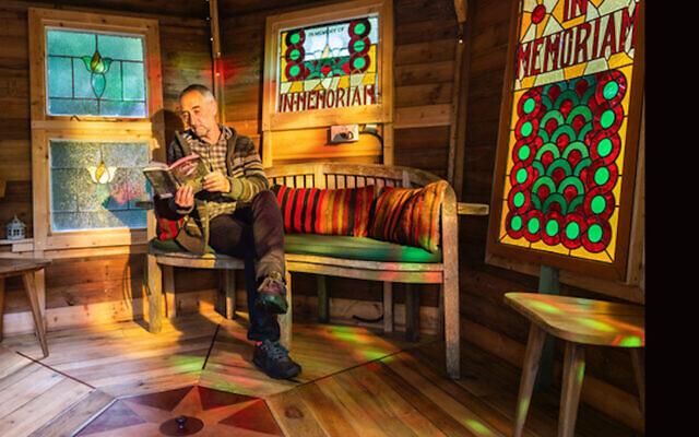 """Les Rowe est assis au milieu de panneaux provenant d'une synagogue de Cardiff dans son abri """"Tranquility Base"""". (Crédit  : Cuprinol via JTA)"""