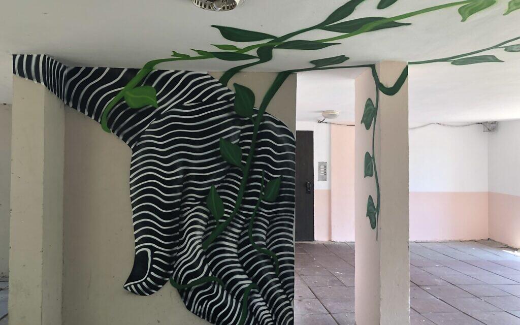 Une vigne tourbillonnante peinte sur les murs de l'entrée d'un immeuble d'habitation fait partie du musée itinérant Zumu à Lod, du 24 au 28 août 2021. (Crédit : Jessica Steinberg/Times of Israel)