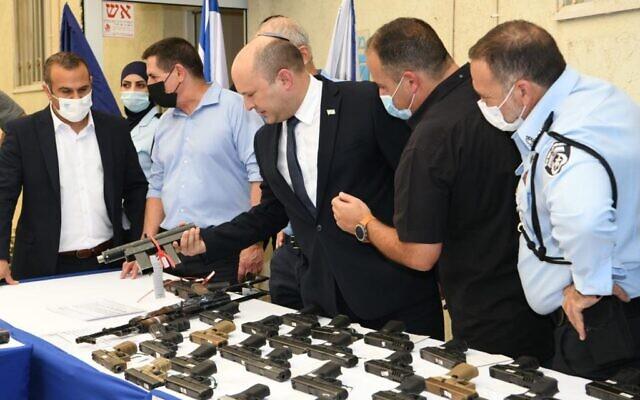 Le Premier ministre Naftali Bennett (au centre) visite un poste de police, le 11 août 2021, pour annoncer un nouveau plan national de lutte contre la criminalité dans le secteur arabe. (Crédit : Amos Ben-Gershom/GPO)