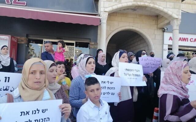 Des Palestiniens et leurs épouses qui demandent des cartes de résidence en Cisjordanie manifestent devant la Commission des Affaires civiles de Ramallah, le 14 juin 2021. (Autorisation : Alaa Mutair)