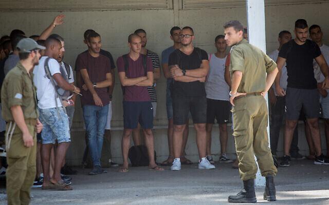 De jeunes hommes israéliens font la queue à leur arrivée au centre de recrutement de Tsahal à Tel Hashomer, le 26 juillet 2018. (Miriam Alster/Flash90)