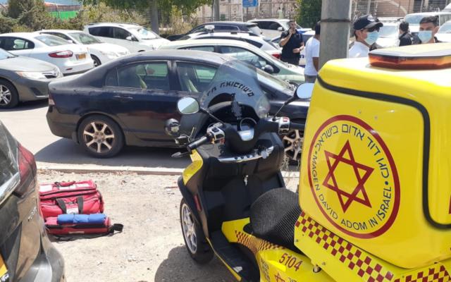 Une ambulance de Magen David Adom devant une voiture dans laquelle un enfant de 6 ans est décédé; dans le conseil régional de Sdot Negev, le 31 août 2021. (Crédit : Magen David Adom)
