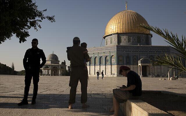 Un officier de la police israélienne (à gauche) monte la garde alors que des Juifs religieux visitent le Mont du Temple dans la Vieille Ville de Jérusalem, le 3 août 2021. (Crédit : AP Photo/Maya Alleruzzo)