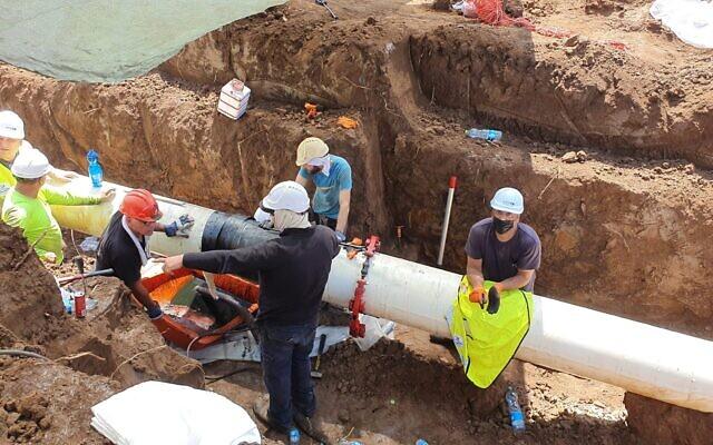 Des employés réparent une canalisation dans le sud d'Israël, propriété de l'entreprise Europe Asia Pipeline Company, suite à une fuite de pétrole brut, le 30 août 2021. (Crédit : Ministère de la Protection environnementale)