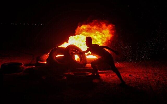 Des Palestiniens font brûler des pneus lors d'émeutes à la frontière entre Israël et Gaza, à l'est de Gaza City, le 30 août 2021. (Crédit : Mohammed Abed/AFP)