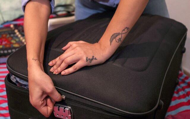 Nanor Abachian ferme ses bagages dans son domicile de Beyrouth avant son immigration à Chypre, le 31 août 2021. (Crédit : ANWAR AMRO / AFP)