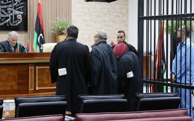 Saadi Kadhafi, à droite, le fils de feu le dictateur Mouammar Kadhafi,  dans la cellule des accusés pendant son procès à Tripoli, en Libye, le 13 mars 2016. (Crédit :  MAHMUD TURKIA / AFP)