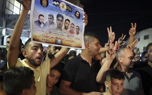 Un Palestinien brandit une affiche montrant les photos des six terroristes palestiniens évadés de la prison Gilboa, lors de réjouissances saluant cette fuite réussie dans le camp de réfugiés de Jénine, dans le nord de la Cisjordanie, le 6 septembre 2021. (Crédit : Jaafar Ashitiyeh/AFP)