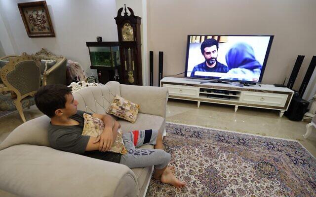 """Un jeune homme regarde un épisode de la série télévisée iranienne """"Gando"""", à Téhéran, la capitale de l'Iran, le 6 septembre 2021. (Crédit : ATTA KENARE / AFP)"""
