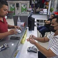 Un Palestinien reçoit une aide financière versée par le Qatar dans un supermarché de Gaza City, le 15 septembre 2021. (Crédit : Mahmud Hams/AFP)