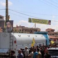 Des gens brandissent des portraits du chef du Hezbollah, Hassan Nasrallah, alors qu'ils se rassemblent pour accueillir des pétroliers transportant du carburant iranien, à leur arrivée de Syrie dans la ville de Baalbeck, dans la vallée de la Bekaa au Liban, le 16 septembre 2021. (Crédit : AFP)