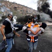 Un manifestant palestinien transporte un jeune garçon à l'écart des affrontements avec les forces israéliennes suite à une manifestation contre les implantations dans le village de Beita, en Cisjordanie, le 17 septembre 2021. (Crédit : JAAFAR ASHTIYEH / AFP)