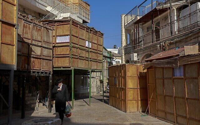 Un ultra-orthodoxe marche devant une souccah, une hutte temporaire construite à l'occasion de la fête juive de Souccot, fête des Tabernacles,  dans le quartier ultra-orthodoxe de Batei Ungarin près du quartier Mea Sharim à Jérusalem, le 20 septembre 2021. (Crédit :  MENAHEM KAHANA / AFP)