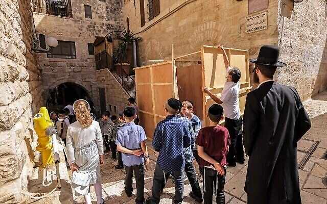 Des résidents juifs établissent une Soucca, une hutte temporaire construite à l'occasion de la fête juive de Souccot, fête des Tabernacles, dans la Vieille Ville de Jérusalem, le 20 septembre 2021. (Crédit : Emmanuel DUNAND / AFP)