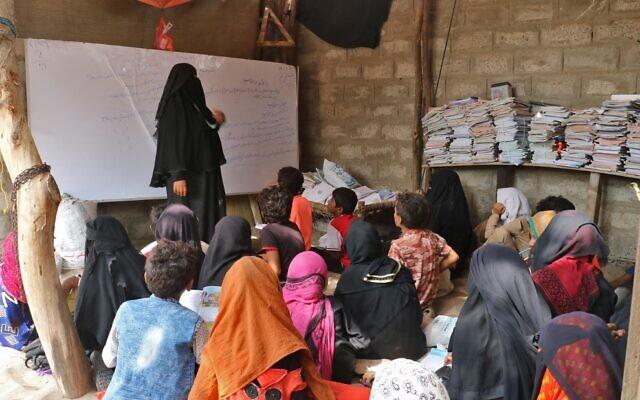 L'enseignante yéménite Amina Mahdi (à gauche) donne une leçon à des enfants affalés sur le sol de sa maison dans la zone rurale de Muhib, dans la province méridionale de Hodeida, le 1er septembre 2021. (Photo de - / AFP)