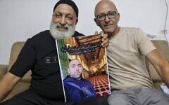 Malek Hassuna (à gauche) montre une photo de son défunt fils Mussa (au centre), abattu le 10 mai, alors qu'il est avec Effi Yehoshua à Lod, le 18 août 2021. (Crédit : AHMAD GHARABLI / AFP)