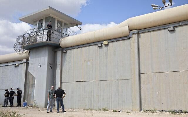 Des policiers et des gardiens de prison inspectent les lieux à l'extérieur de la prison de Gilboa, dans le nord d'Israël, le 6 septembre 2021, après l'évasion de six détenus palestiniens. (Crédit : AP Photo/Sebastian Scheiner)