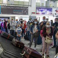 Des voyageurs attendent de récupérer leurs bagages à l'aéroport international de Heraklion, sur l'île de Crète, le 14 mai 2021. (Crédit : AP Photo/Harry Nakos, File)