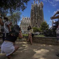 Des touristes prennent des photos devant la basilique Sagrada Familia créée par l'architecte Antoni Gaudi à Barcelone, en Espagne, le vendredi 9 juillet. (Crédit :  AP Photo/Joan Mateu)