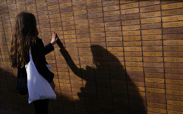 Une femme touche l'une des pierres du du nouveau monument, en hommage aux victimes du nazisme et de la collaboration aux Pays-Bas pendant la Shoah, et situé au cœur du quartier juif historique d'Amsterdam, le dimanche 19 septembre 2021. (Crédit : AP Photo/Peter Dejong)