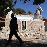 Un résident passe devant une église grecque orthodoxe endommagée après un fort séisme dans le village d'Arcalochori, en Crète, une île du sud de la Grèce, le 27 septembre 2021. (Crédit : AP Photo/Harry Nikos)