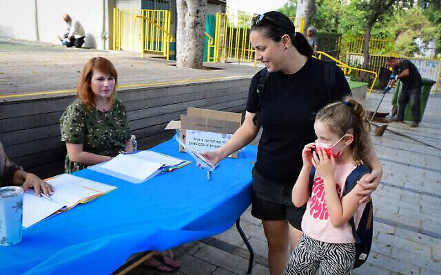 Un parent récupère un kit de test rapide COVID avant l'ouverture de la nouvelle année scolaire, à Tel Aviv, le 30 août 2021. (Crédit : Avshalom Sassoni/Flash90)
