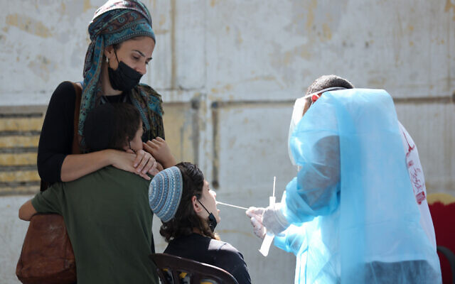 Des personnels de santé font un test de dépistage à la cOVID-19 sur des Israéliens qui veulent se rendre à l'étranger dans un centre temporaire de Safed, dans le sud d'Israël, le 31 août 2021. (Crédit : David Cohen/Flash90)