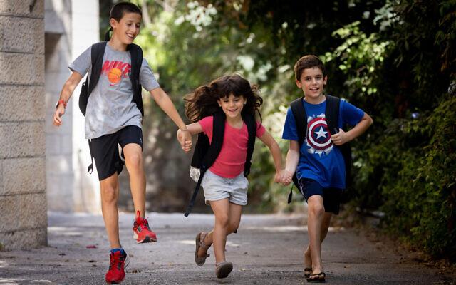Des enfants israéliens courent en portant leur cartable à la veille de la rentrée scolaire à Jérusalem, le 31 août 2021. (Crédit : Yonatan Sindel/Flash90)