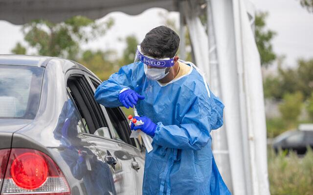 Des employés pratiquent des tests à la COVID-19 dans un centre de dépistage de type Drive-in à Modiin, le 10 septembre 2021. (Crédit : Yossi Aloni/Flash90)